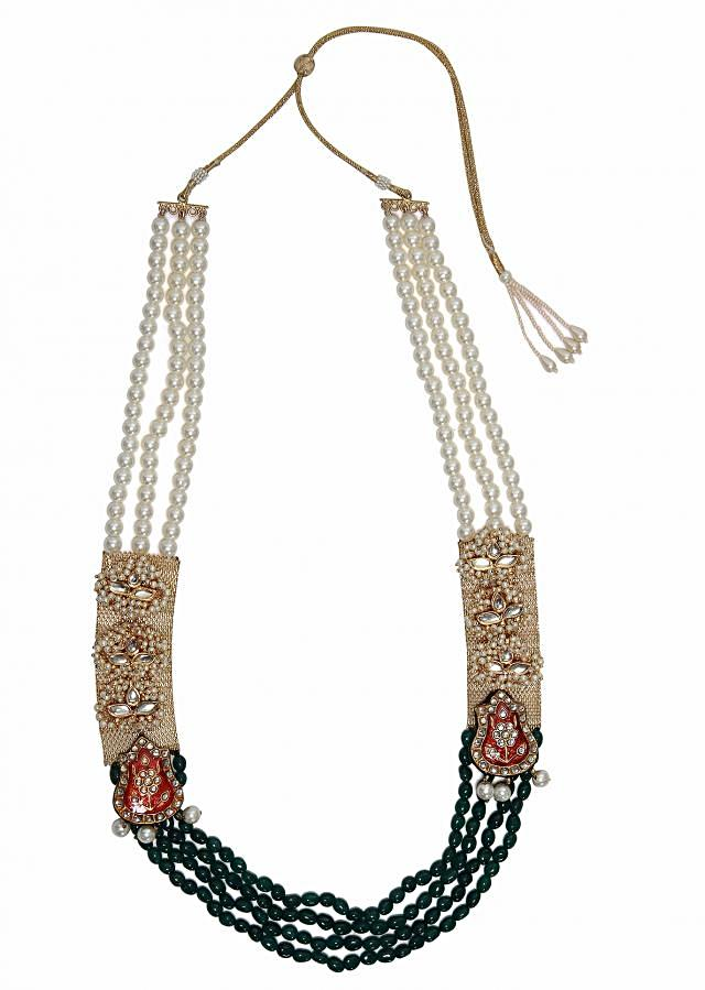Inspired by the mughals, this rajwada neckpiece has delicate kundan pieces on a gold base surrounded by pearls. The red enamel and kundan studded motifs added to the elegance of this neckpiece. The neckpiece has strands of jade and faux pearl.