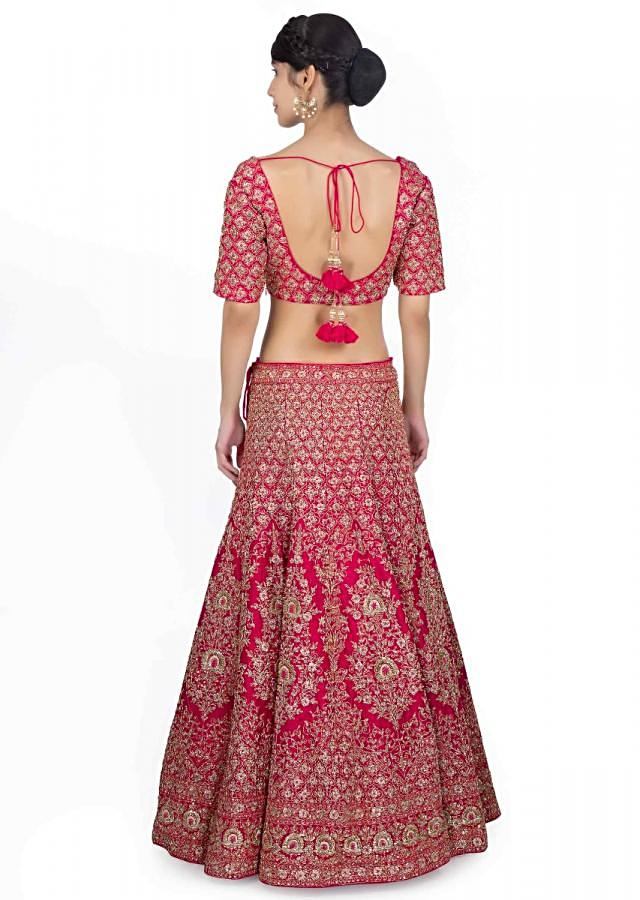 Rani pink raw silk heavily embellished lehenga paired with embroidered blouse and powder pink net dupatta only on Kalki