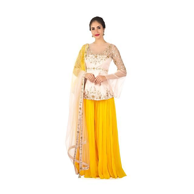 Raw silk yellow pleated palazzo paired with a powder pink long blouse only on Kalki