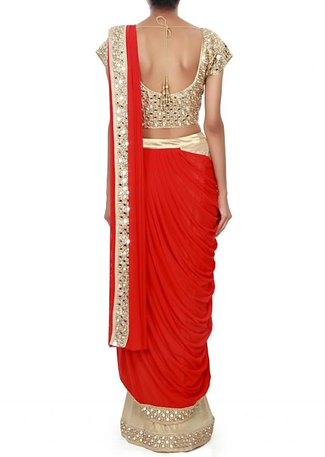 Red and gold saree gown enhanced in mirror and kundan embroidery only on Kalki