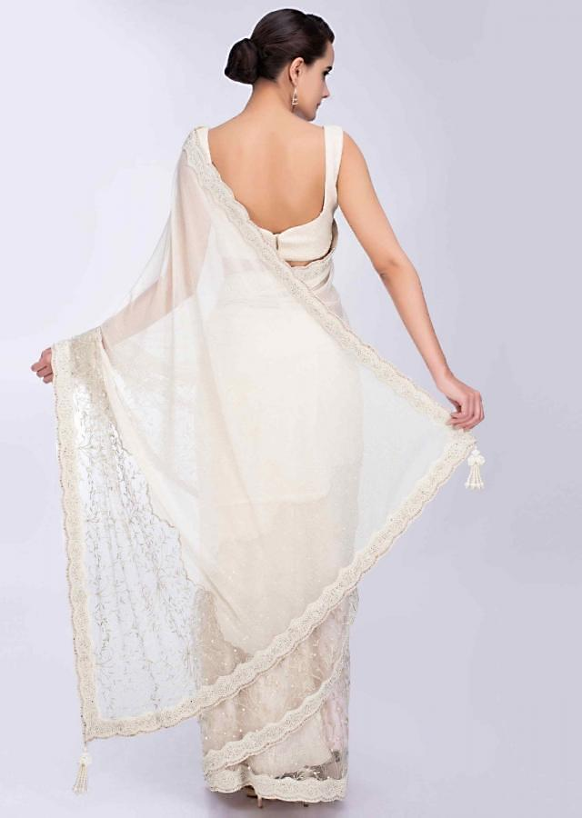 Scallop embroidered half and half ivory saree featuring in net and shimmer lycra only on Kalki