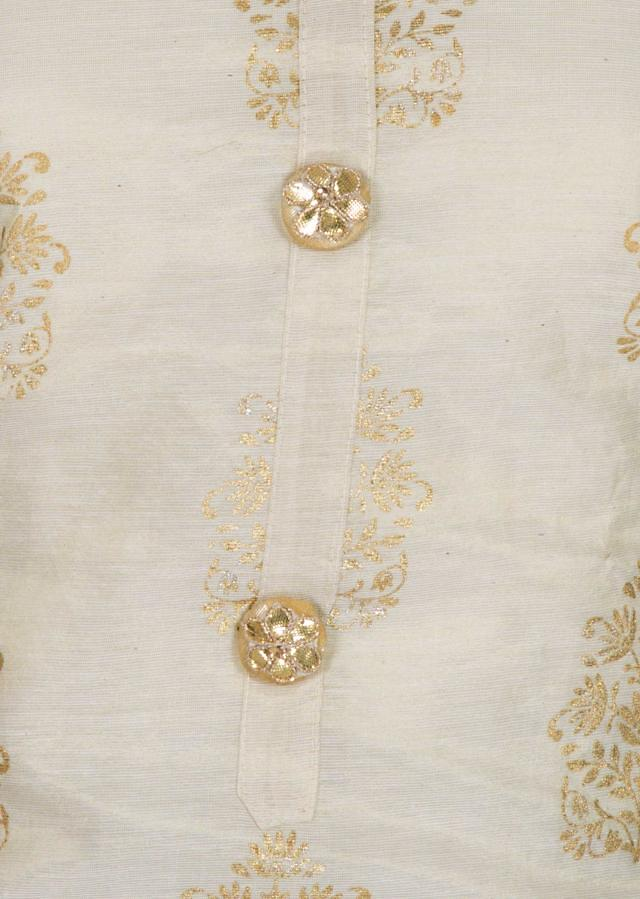 Semi stitched suit in beige with foil print and fancy buttons only on Kalki