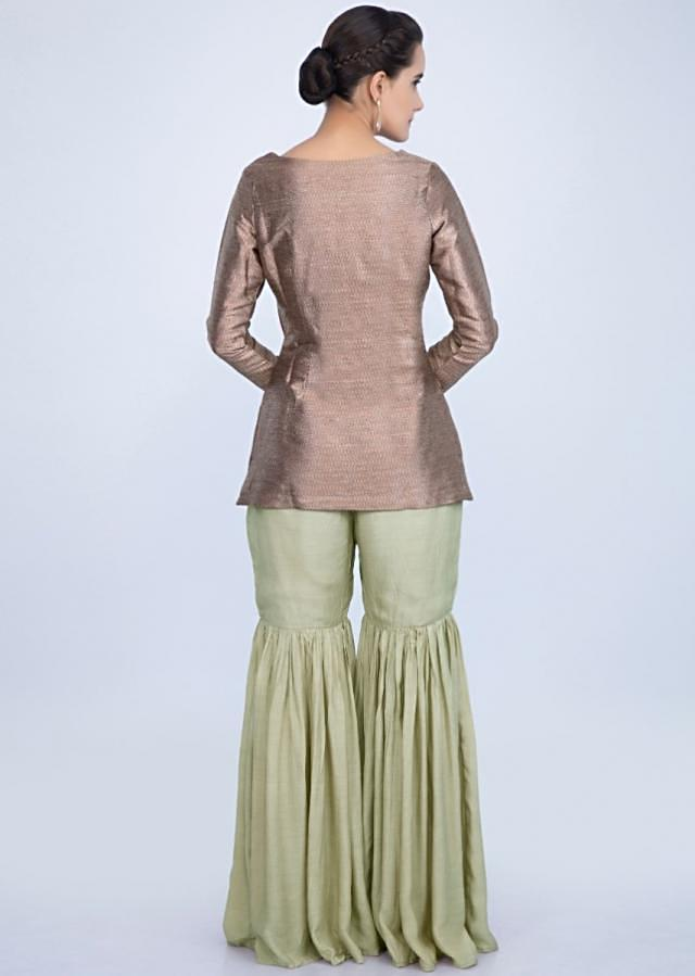 Sharara set featuring with copper brocade top and heavy embroidered net dupatta only on Kalki