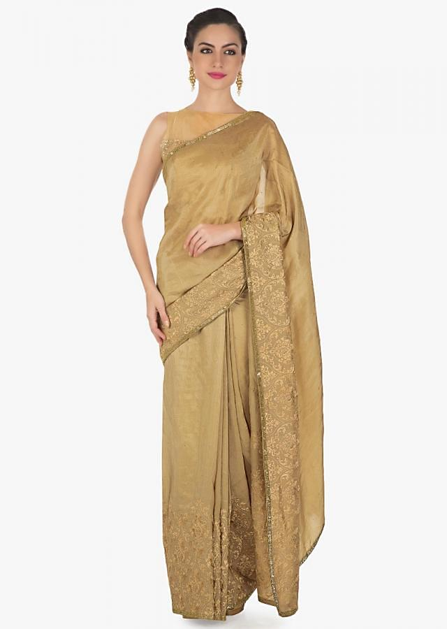 Tan beige saree in silk embellished in resham and cut dana  border only on Kalki