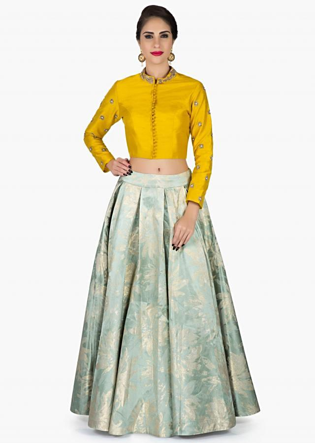 The Uncommon Grass Blue Brocade Lehenga Teamed up with Full sleeve Yellow Blouse only on Kalki