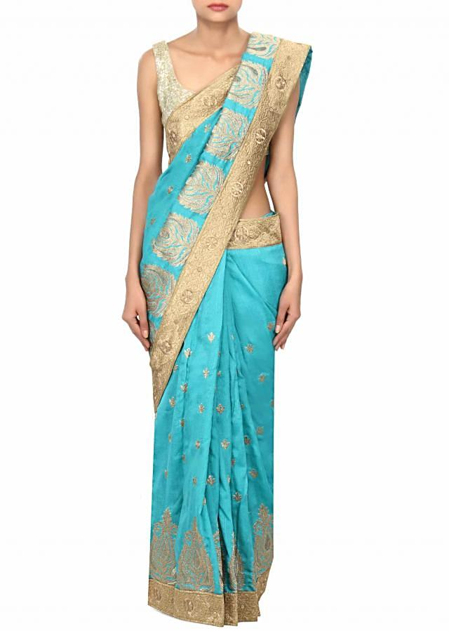 Turq saree enhanced in zari embroidered butti only on Kalki