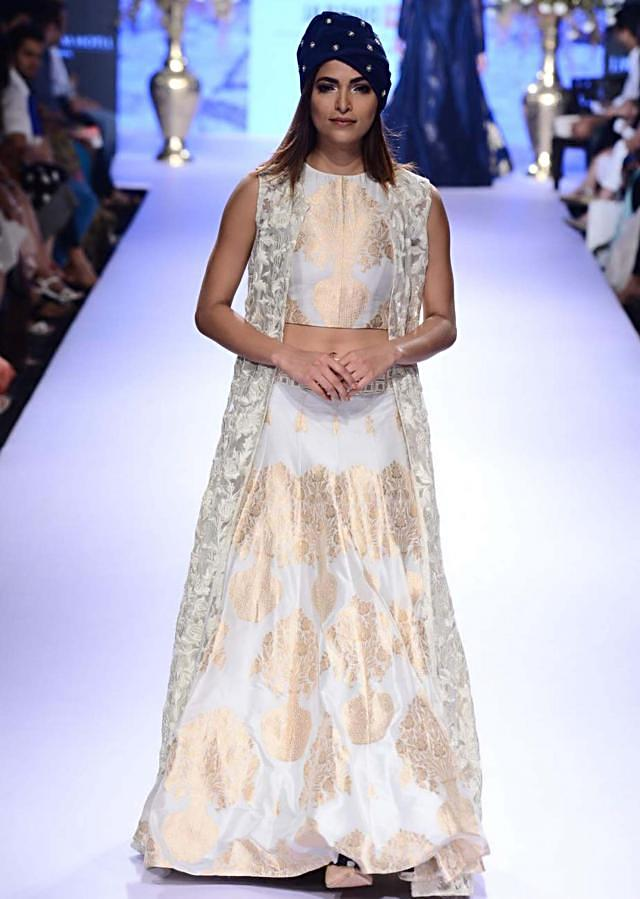 Model walks the ramp in white lehenga adorn in foil print matched with long jacket for SVA collection named Istanbul at Lakme Fashion Week Summer Resort 2015