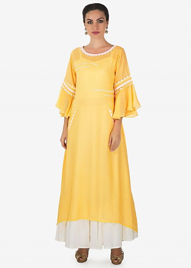 White long kurti matched with yellow top layer highlighted in fancy buttons only on Kalki