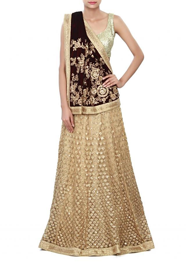 Merlot wine and dusty beige lehenga saree enhanced in zari and sequin embroidery only on Kalki