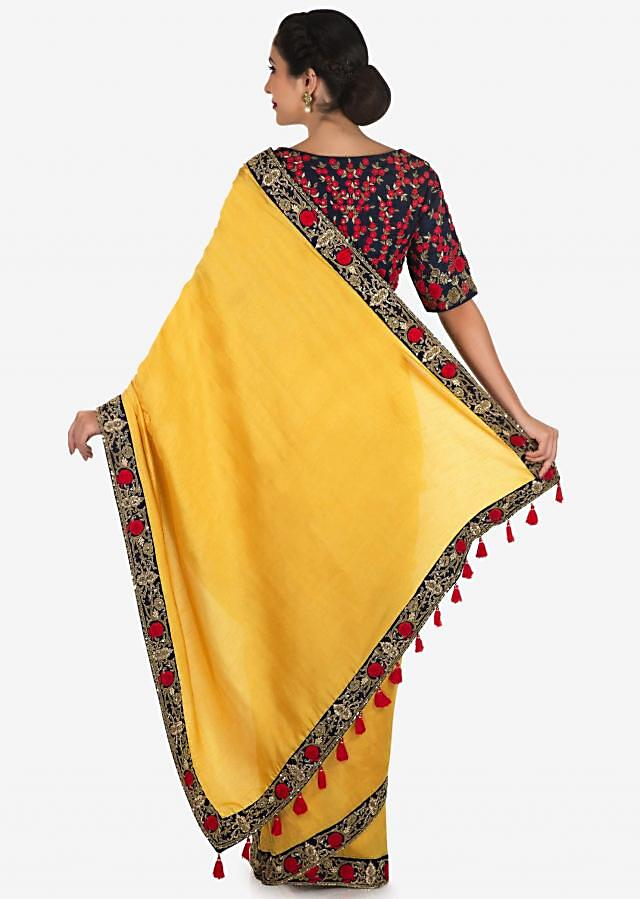 Yellow saree in satin silk with a navy blue blouse embroidered with zardosi and thread work only on Kalki