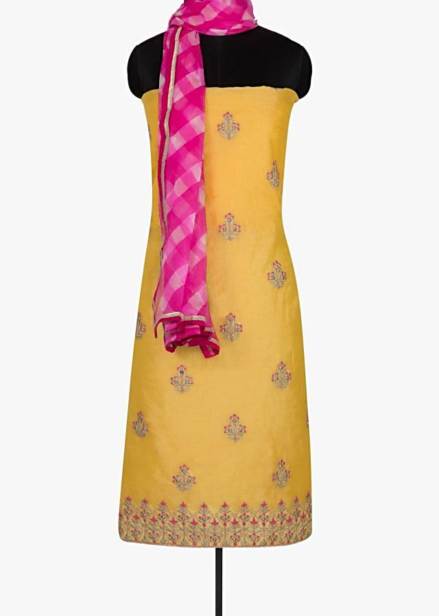 Yellow unstitched suit in zari butti and pink leheriya dupatta only on Kalki