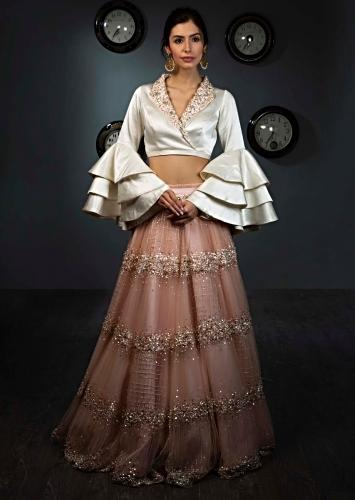 3cf7307aa1 White satin blouse with layered frill sleeves paired with peach net skirt  in moti and sequins