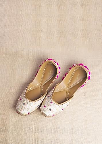 Champagne Gold Juttis In Heavy Linen With Vibrant Bead Work In Flower And Leaf Motifs By Vareli Bafna