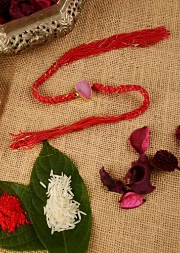 Fire Brick Colored Braided Rakhi In Gold And Red Thread Work Is Further Enhanced In Semi-Precious Pink Stone  By Kohar