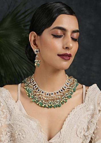 Gold Pleated Necklace Set With Kundan Flowers Studded With Blue Stones And Dangling Green Bead And Moti Fringes By Paisley Pop