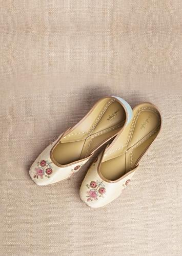 Light Gold Juttis In Raw Silk With Embroidered Multicolored Floral Motifs Using Sequins And Resham Work By Vareli Bafna