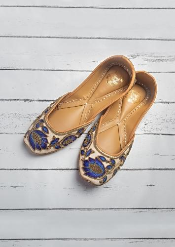 Off White Juttis In Linen With Blue Resham Work, Gold Beads And A Hit Of Swarovski By Vareli Bafna