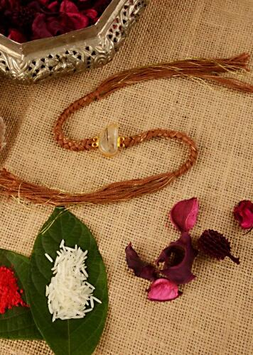 Russet Brown Braided Rakhi In Gold And Brown Thread Work Is Further Enhanced In Semi-Precious Stone By Kohar